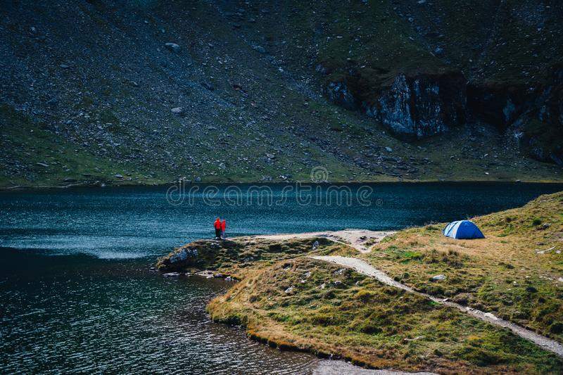 View couple of tourists stand adove the lake. adventures Camping tourism and tent. landscape near water outdoor at Lacul Balea royalty free stock image