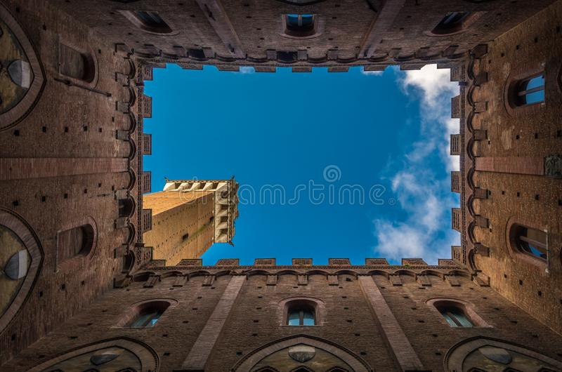 View from the courtyard of medieval Siena town hall, Palazzo Pubblico, to Mangia Tower, Torre del Mangia, and blue sky, Tuscany, royalty free stock photo