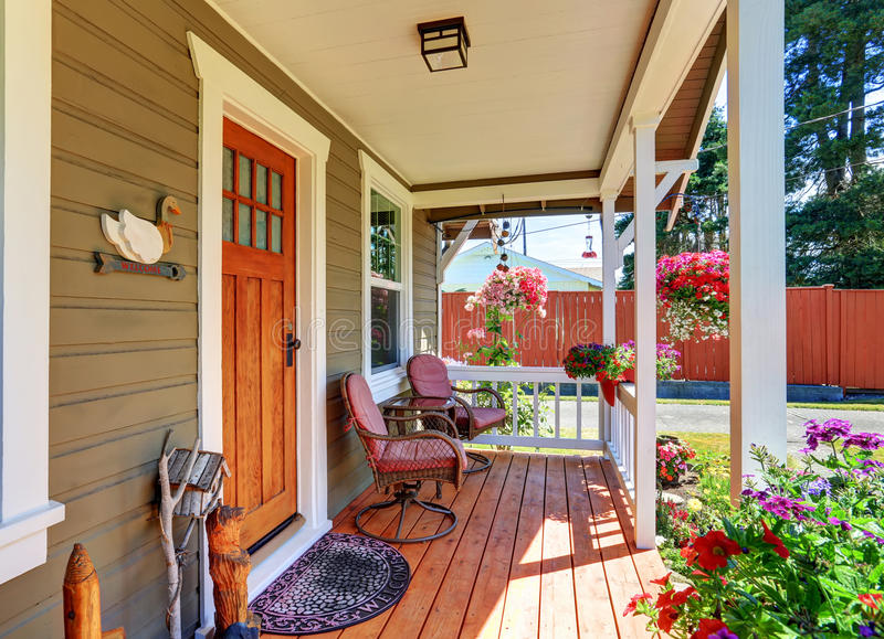 View of cozy covered porch with chairs and flower pots. View of cozy small covered porch with chairs and flower pots. Northwest, USA stock image