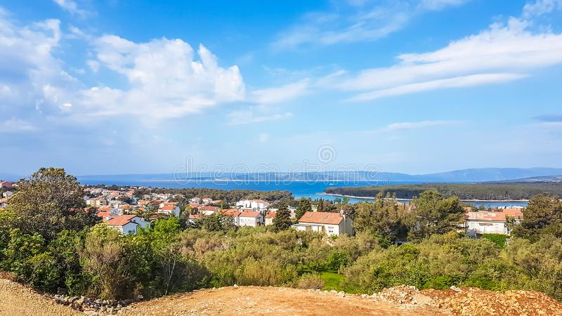 Punat -  remote view on Punat. A view on Croatian coastal line from a small hill. Below there is a small city, located directly by the seashore. All the rooftops stock images