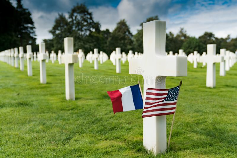 View of cross headstones in the American Cemetery at Omaha Beach in Normandy with French and US flags royalty free stock photo