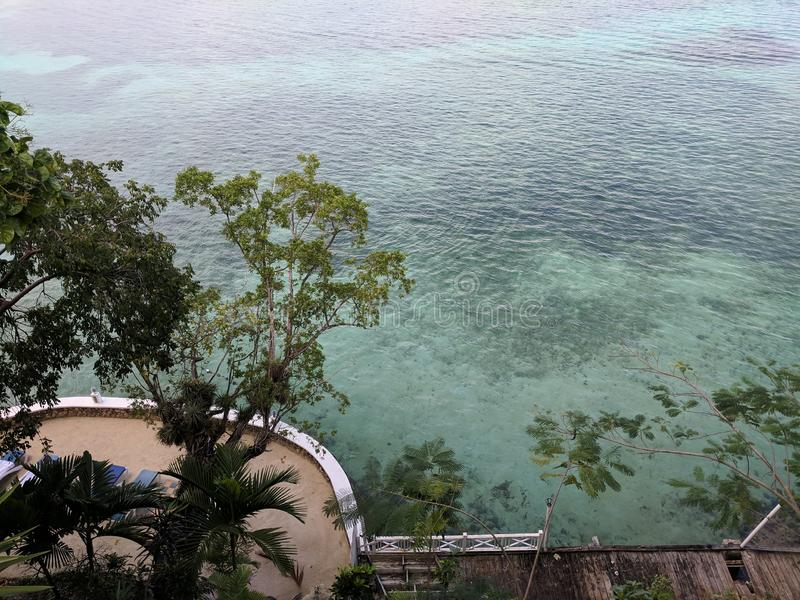 View of crystal clear blue green sea off Jamaica. With patio deck and trees below stock photos