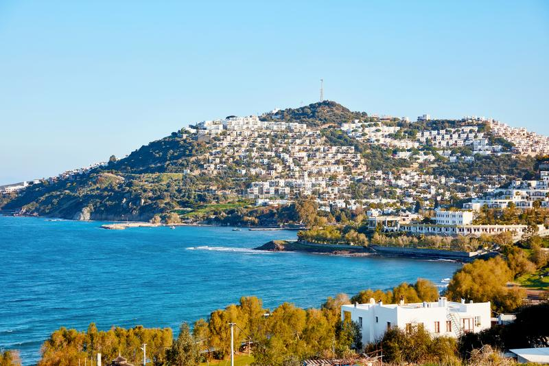View of Cukurbuk bay and the white Aegean house settlements over. The mountain in Gumusluk, Bodrum, Mugla, Turkey royalty free stock photos