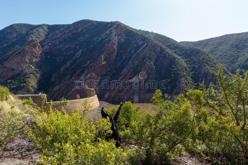 The view of the dam with bushes and mountains royalty free stock photos