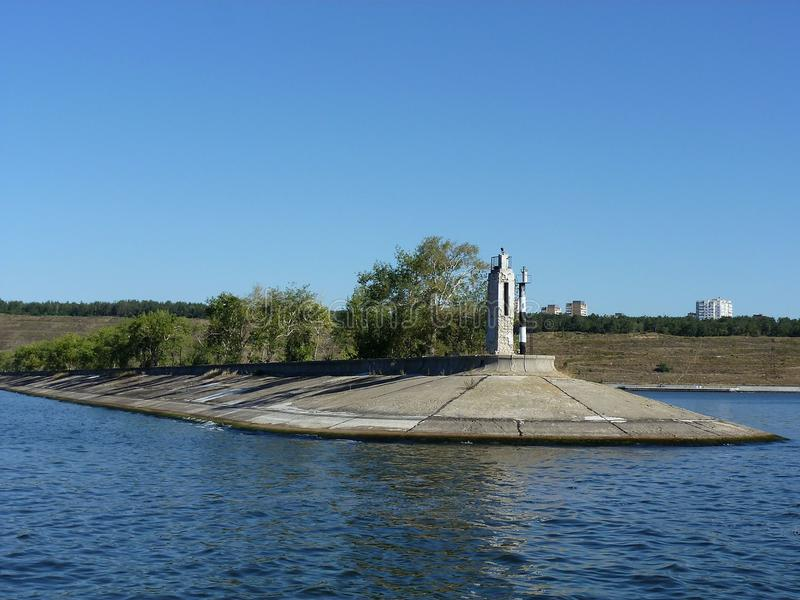 View of the dam near Tolyatti. The breakwater with the lighthouse and trees at the entrance to the river port of Tolyatti stock photography