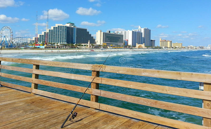 Daytona Beach from the pier, fishing pole. A view of Daytona beach from the pier with a fishing pole in the foreground and lots of blue ocean and sky stock image