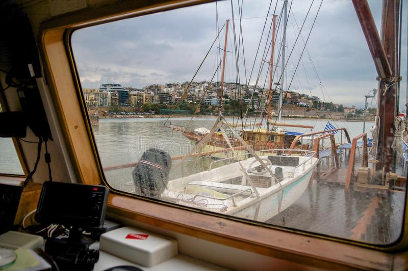 View of the deck of a ship and Kastela city of Piraeus during a rainy day through glass with water drops stock photo