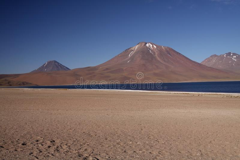 View on deep blue lake at Altiplanic Laguna Lagoon Miscanti in Atacama desert with partly snow capped cone of volcano stock image