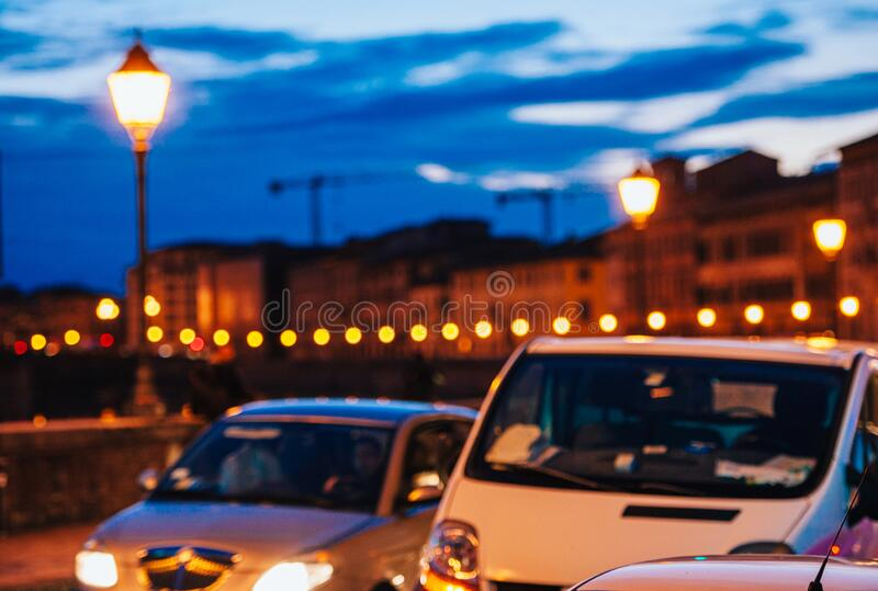 View of defocused cars driving fast on Florence bridge at dusk. View of defocused cars driving fast on Florence bridge with dusk blue cloudy sky in background royalty free stock photography