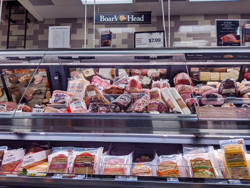 View of a deli meat display inside a QFC grocery store, featuring Boar`s Head salami, turkey, ham, and other meats. Kirkland, WA / USA - circa December 2019 royalty free stock image
