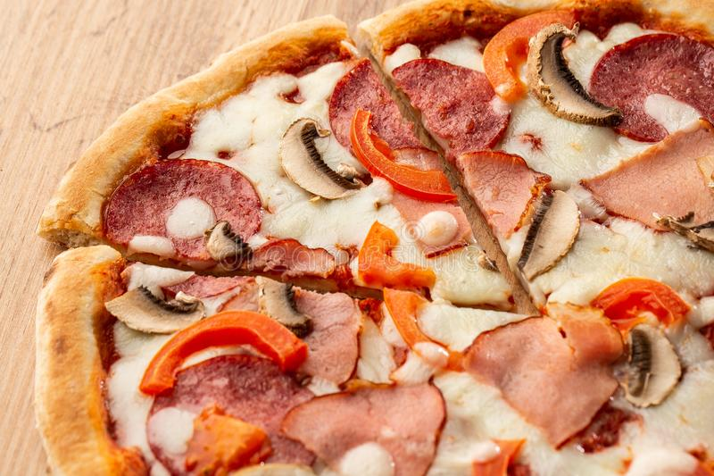 Top view of delicious Capricciosa Pizza on wooden table. Ingredients peeled tomato, cheese, ham, mushrooms, salami. stock image