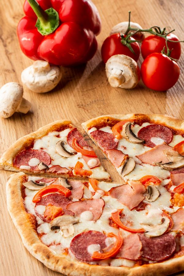 Top view of delicious Capricciosa Pizza on wooden table. Ingredients peeled tomato, cheese, ham, mushrooms, salami. stock photography