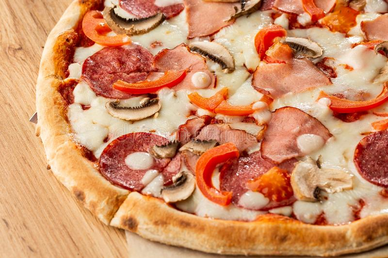 Top view of delicious Capricciosa Pizza on wooden table. Ingredients peeled tomato, cheese, ham, mushrooms, salami. royalty free stock photography