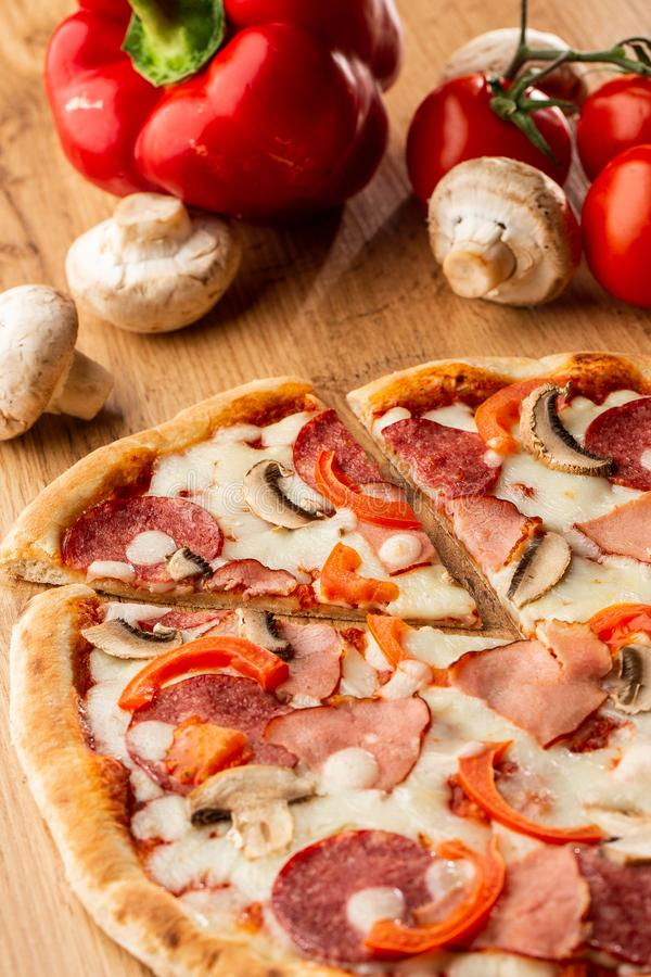Top view of delicious Capricciosa Pizza on wooden table. Ingredients peeled tomato, cheese, ham, mushrooms, salami. stock images