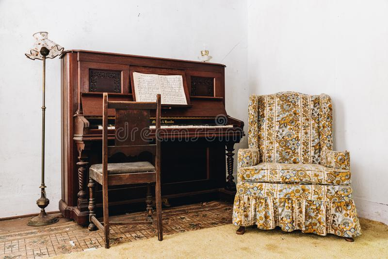 Derelict Antique Piano, Floor Lamp + Padded Chair - Abandoned House in Catskill Mountains - New York. A view of a derelict antique piano, floor lamp, and floral royalty free stock photography