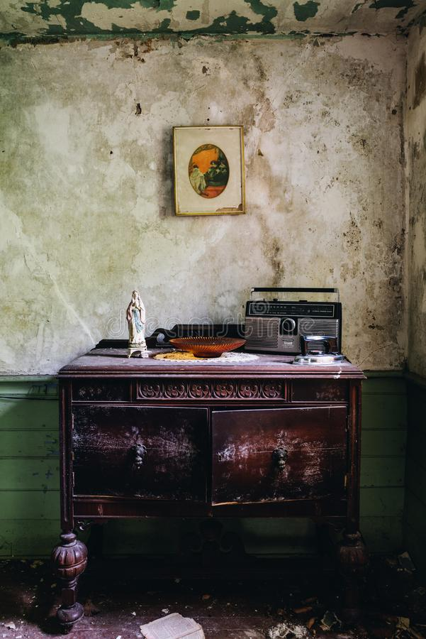 Derelict Antique Wood Table + Radio - Abandoned House in Catskill Mountains - New York. A view of a derelict antique wood table with a small statue and vintage stock images