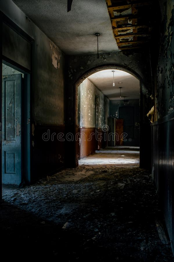 Derelict Hallway - Abandoned Knox County Infirmary - Ohio. A view of a derelict hallway at the abandoned Knox County Infirmary near Mt. Vernon, Ohio royalty free stock image