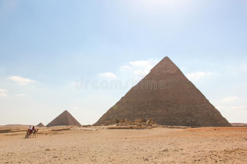 View from the desert on a series of pyramids, the three pyramids of the Giza complex with marching riders stock image