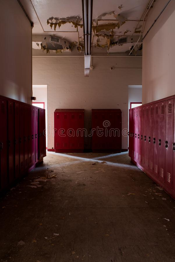 Desolate Hallway + Red Lockers - Abandoned Gladstone School - Pittsburgh, Pennsylvania. A view of a desolate hallway junction with red lockers inside the stock photos