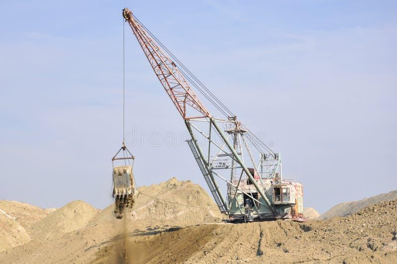 Digging mining excavator at work in quarry. View of digging mining excavator at work in quarry royalty free stock image