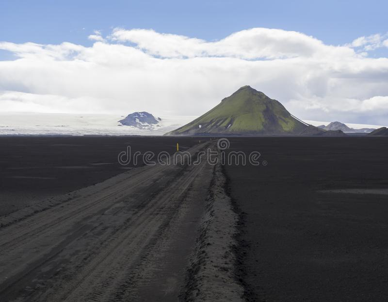 View on dirt mountain road F210 in black lava sand desert at Nat. Ure reserve Fjallabak in Iceland with green Maelifell mountain and myrdalsjokull glacier, blue stock image