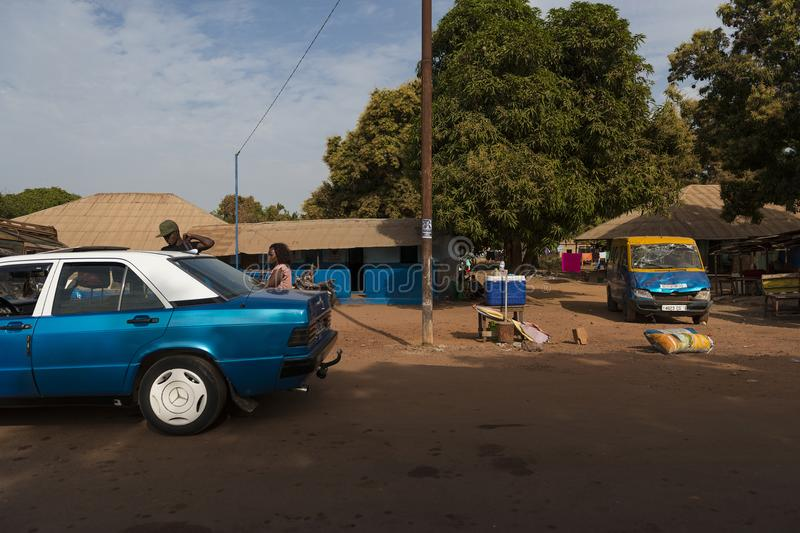 View of a dirt road in a street of a slum in the city of Bissau with people entering in a taxi, in Guinea-Bissau. Bissau, Republic of Guinea-Bissau - January 28 stock photography