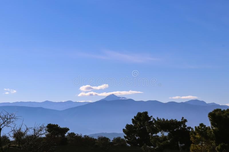 View of distant blue mountains of Peloponnese in Greece under blue sky with a few clouds and dark green trees in foreground.  royalty free stock photography