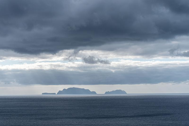 A view of a distant island, sunbeams passing through the clouds. A view of a distant island, sunbeams passing through dramatic stormy grey clouds above stock images