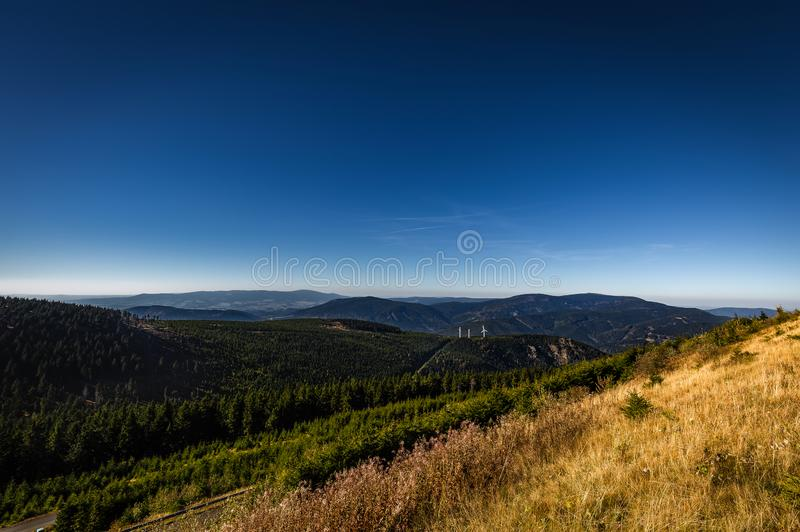 View from Dlouhe strane top reservoir to valley with wind turbine and green forest, dark blue sky.  royalty free stock photo