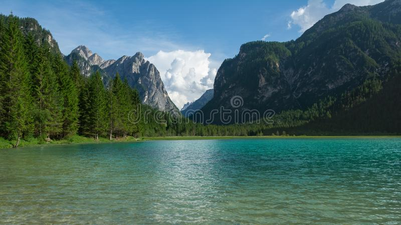 View of Dobbiaco Lake and surrounding mountains. Dolomites, Italy.  stock photo