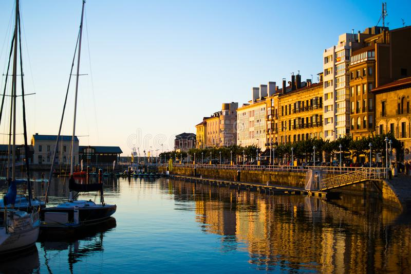 View of the dock of Gijon, Asturias, Spain, with reflections in the water, in Cimadevilla, the old town, during the sunset. stock photography