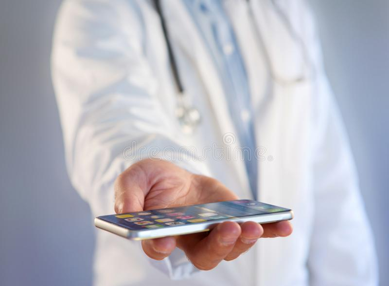 Doctor using smartphone on a color background. View of a Doctor using smartphone on a color background royalty free stock images