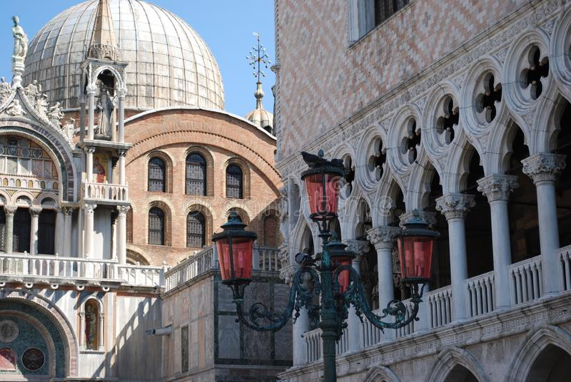 The view of Doge`s Palace & St Mark`s Basilica, Venice, Italy with a decorative lamp post in the foreground. This view includes parts of both the Doge`s Palace royalty free stock image