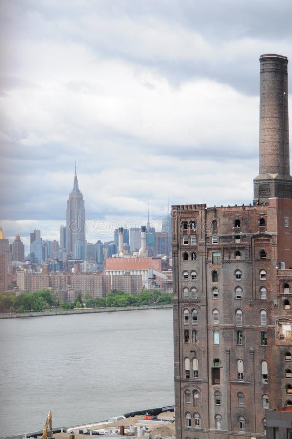View of the Domino sugar Refinery, Manhattan and the East River royalty free stock images
