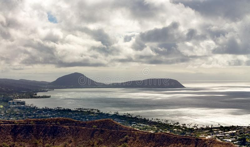 View of the dormant Koko Head Crater, Oahu, Hawaii. And Kaihuokapuaa Cape from Diamond Head Crater across a tranquil Pacific Ocean under a cloudy sky stock image