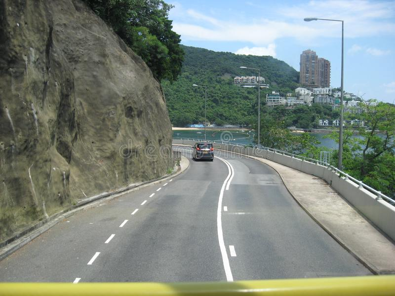 View from a double decker bus near Repulse bay, Hong Kong. The view from the top of a double decker bus of the scenic winding road near Repulse bay, Hong Kong royalty free stock photo