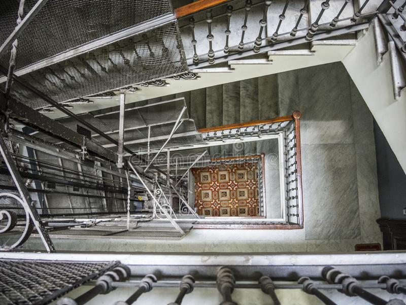 Elevator shaft surrounded by marble stairs stock image