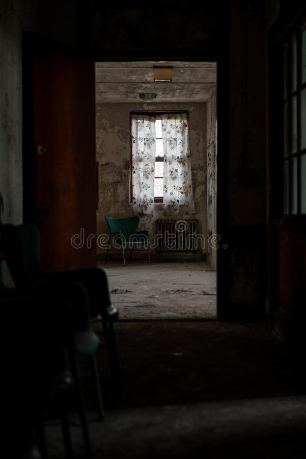 Derelict Room with Green Plastic Chair, Radiator & Curtains - Abandoned Westboro State Hospital - Massachusetts. A view down a hallway towards a derelict room royalty free stock image