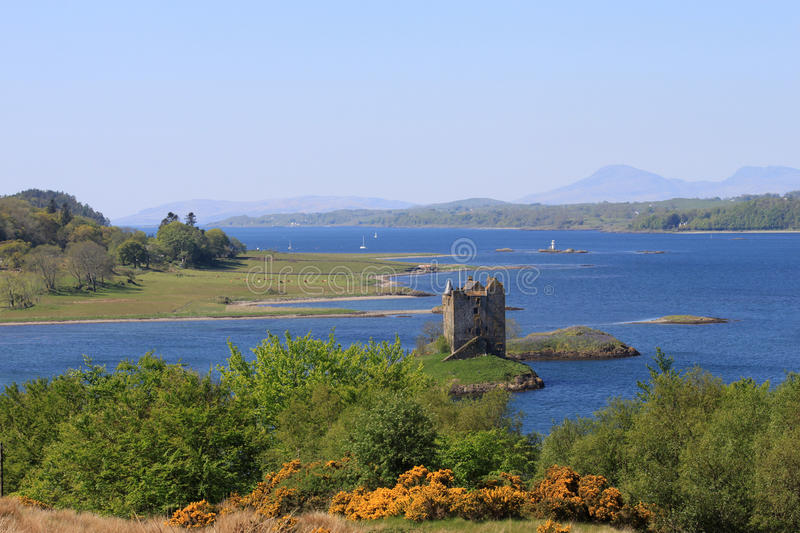 View down Loch Linnhe past Castle Stalker to Mull. View of Castle Stalker from near Portnacroish looking South West across the mouth of Loch Laich and down Loch stock image