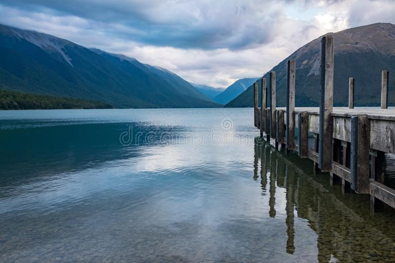 A view down the side of a wooden jetty of the incredibly beautiful Rotoiti Lake surrounded by mountains. stock photo