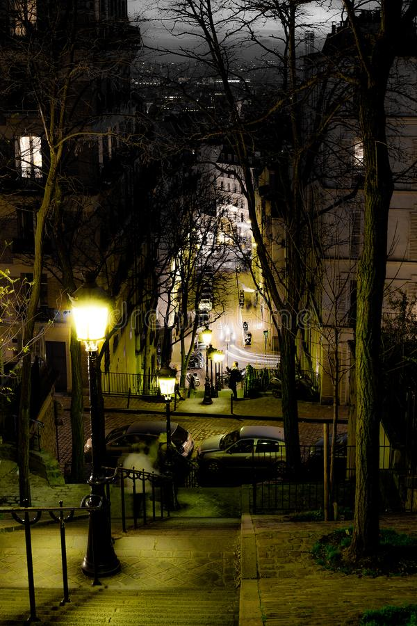 View down steep steps on a hillside in a city. At night with illuminated street lamps and an avenue of bare leafless trees in winter with townhouses and parked stock photo