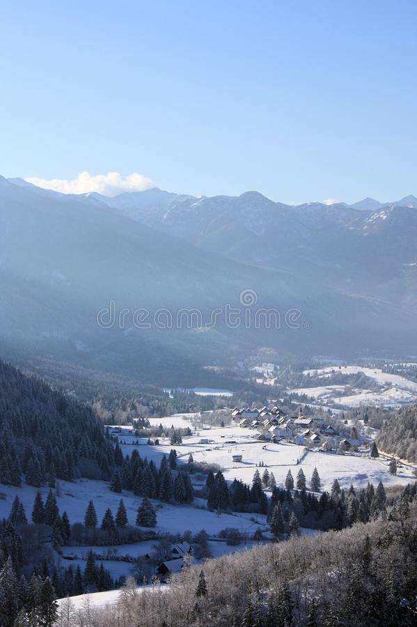 View down to village and valley behind. Village Nemški rovt sunlit in winter time, Bohinj Slovenia royalty free stock photo