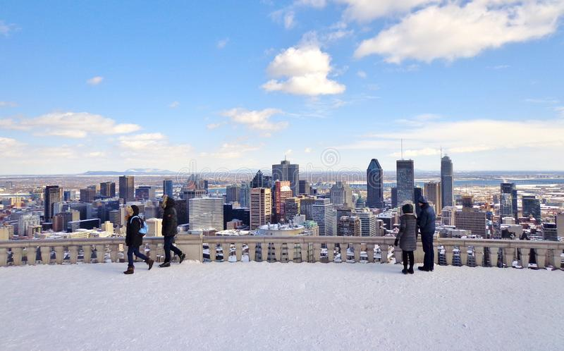 View of Downtown Montreal, Canada Winter. Wide shot of people gazing at the skyline of downtown Montreal from hilltop overlook on a clear winter day - Montreal stock photo