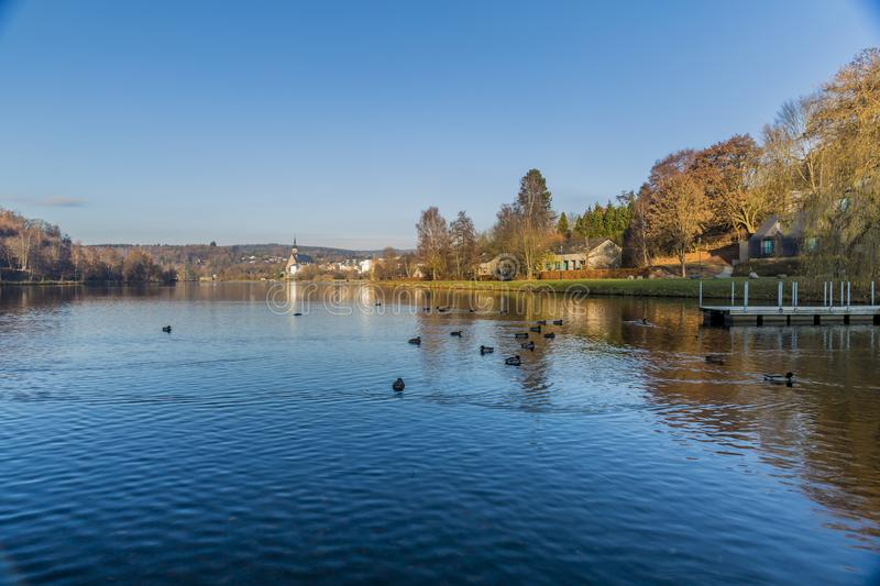 View of the Doyards lake with a wonderful reflection with ducks swimming in the wate. Beautiful view of the Doyards lake with a wonderful reflection with ducks royalty free stock image