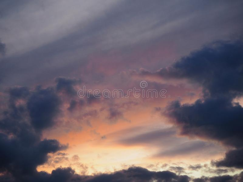 View of the dramatic sky at sunset with dark blue clouds and pink, purple and yellow flashes. From the sun`s rays stock photography