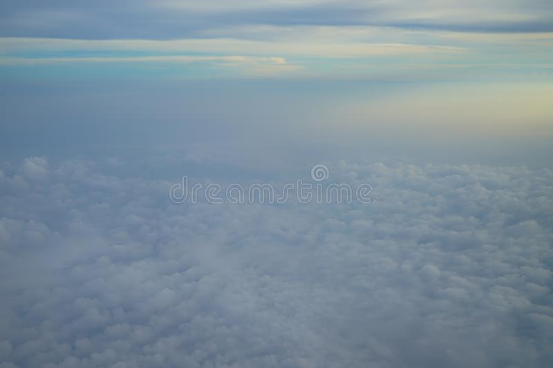 View of dreamy abstract white cloud with blue sky and sunrise light background from airplane window. View of dreamy abstract white cloud with blue sky and stock image