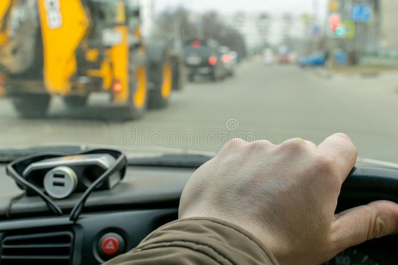 Driver hand on the steering wheel of a car. View of the driver hand on the steering wheel of a car that rides on a city road on the background of a passing stock photography