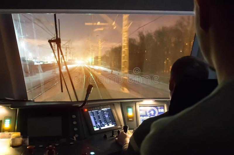 View from the driver& x27;s cab of an electric train, a night voyage on a railway. stock image