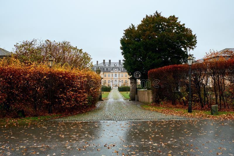 View of a driveway and gated entrance of old residential buildings.  stock photos
