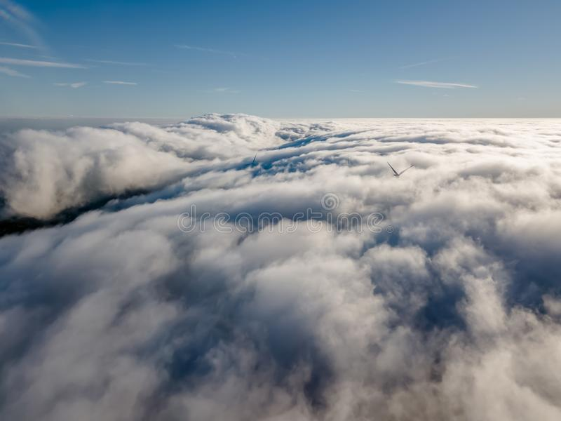 View of a drone above the fog, wind turbines with fog and blue sky stock image